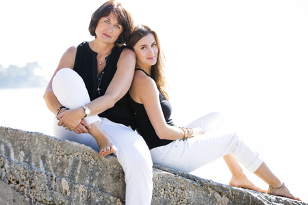 caucasian mother and daughter together on the beach