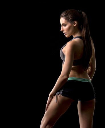 beautiful black woman: pretty caucasian fitness woman on black isolated background