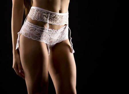 sexy nude women: sexy woman wearing white lingerie on black background Stock Photo
