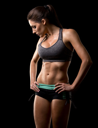 sports bra: pretty caucasian fitness woman on black isolated background
