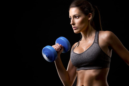 woman muscle: pretty caucasian fitness woman on black isolated background