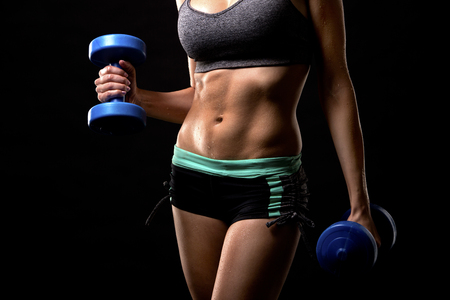strength training: pretty caucasian fitness woman on black isolated background