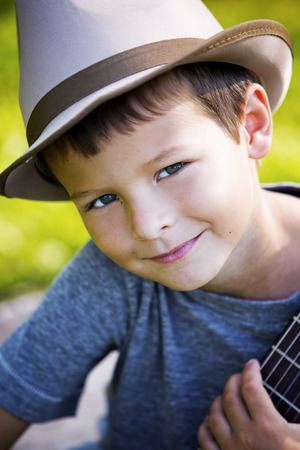 boy kid: cuacasian boy with guitar in the park outdoors