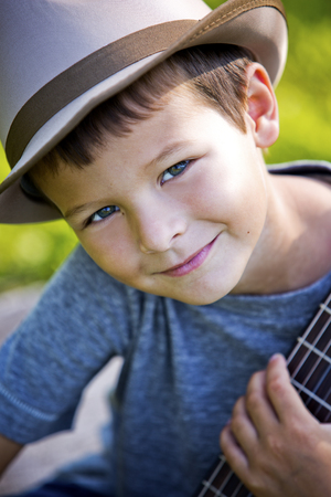 cool kids: cuacasian boy with guitar in the park outdoors