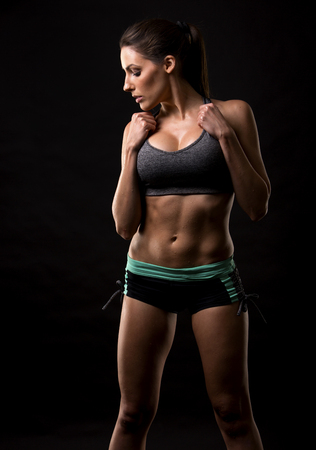 pretty black woman: pretty caucasian fitness woman on black isolated background