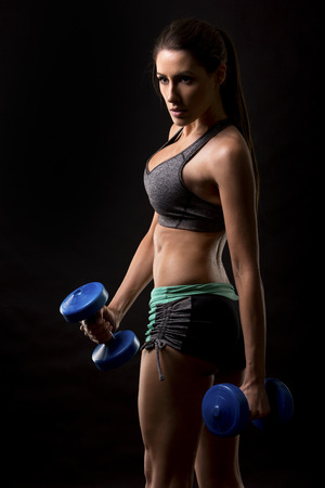 sports training: pretty caucasian fitness woman on black isolated background