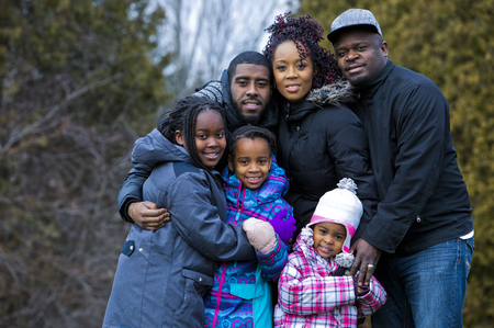 winter people: casual winter young black family outdoors in the park