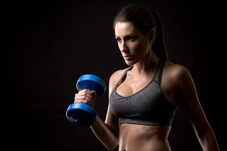 pretty caucasian fitness woman on black isolated background