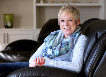 caucasian middle aged woman sitting on sofa at home Stock Photo