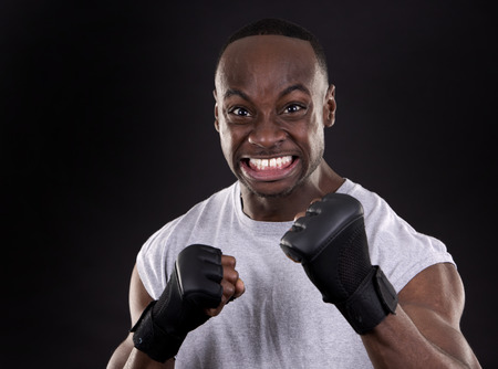 young black fighter wearing gloves on dark background