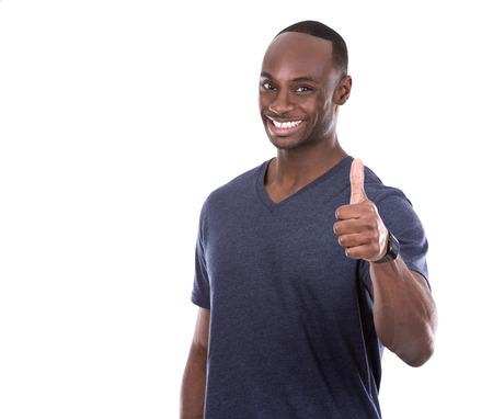 jóvenes excitados Hombre negro ocasional que da los pulgares para arriba en el fondo blanco Foto de archivo