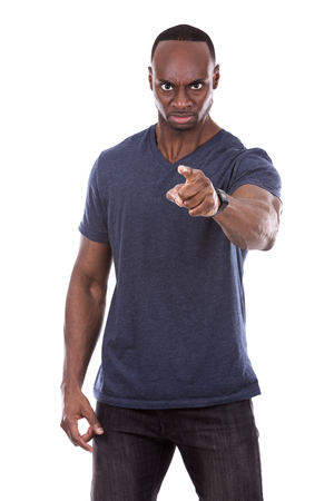 pointing: young casual black man wearing blue tshirt on white background