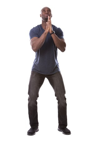 hoping: young casual black man scared and hoping on white background Stock Photo