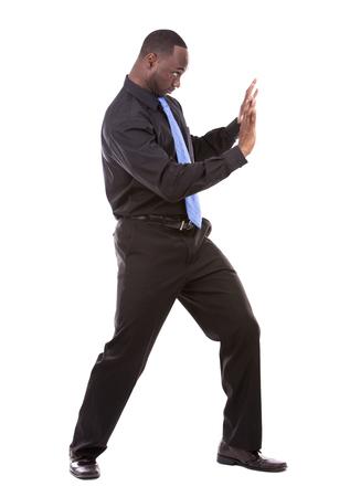 man pushing: young business black man pushing object on white background Stock Photo