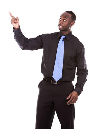hombres de negro: excitado joven mano ocasional del hombre que apunta negro sobre fondo blanco Foto de archivo