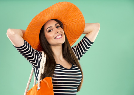 young woman wearing dress and orange hat on green background