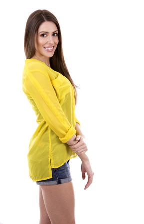 yellow shirt: young woman wearing yellow shirt on white background Stock Photo