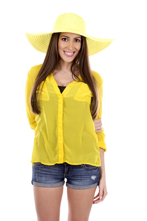 yellow shirt: young woman wearing yellow shirt and hat on white background
