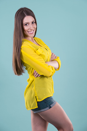 Caucasian woman: young woman wearing yellow shirt on blue background