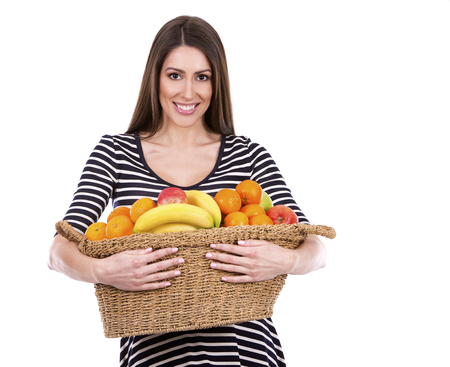 corbeille de fruits: jeune femme caucasien tenant un panier de fruits sur fond blanc Banque d'images