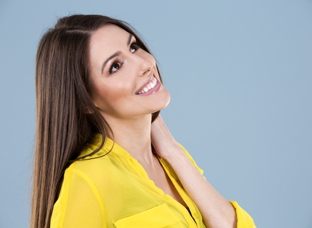 yellow shirt: young woman wearing yellow shirt on blue background