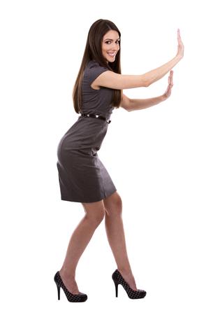 empujando: joven vestido de negocios usando caucásica mujer sobre fondo blanco Foto de archivo
