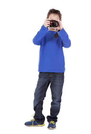 six years: six years old boy taking photos with his camera on white background