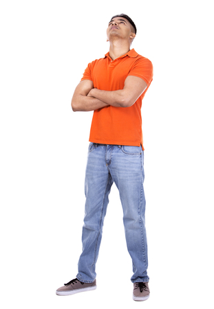 looking around: young casual man wearing orange tshirt on white isolated background Stock Photo