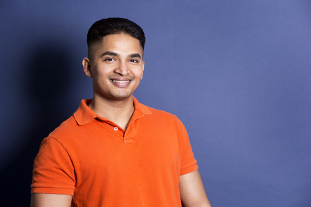 young casual man wearing orange tshirt on blue background