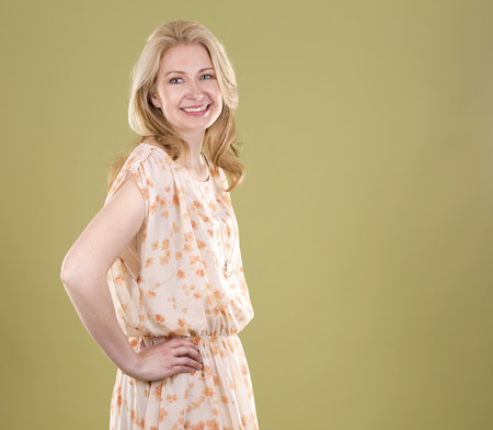 spring green: blond woman wearing beige dress on green background Stock Photo