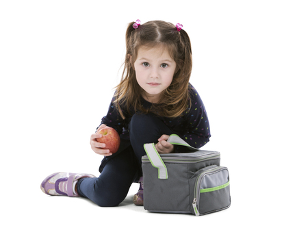 small girl: little girl holding bag with her lunch and apple