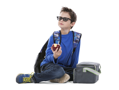 school boy: young boy student with backpack and apple in his hand on white background