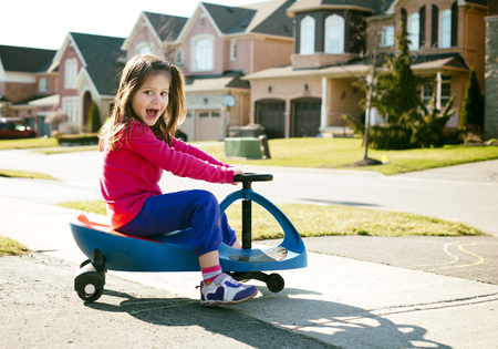 small girl is having fun riding his toy on the street photo