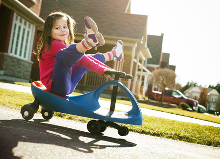 small girl: small girl is having fun riding his toy on the street