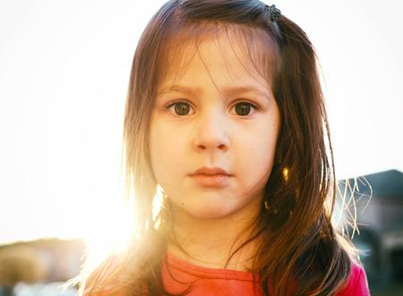 little girl having fun outdoors wearing pink shirt during sunset photo