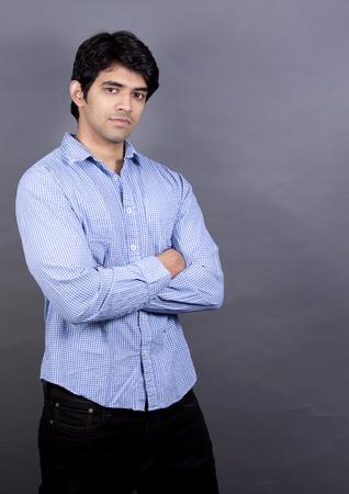 gut aussehend ostindischen Mann blaues Hemd auf hellgrauem Hintergrund trägt
