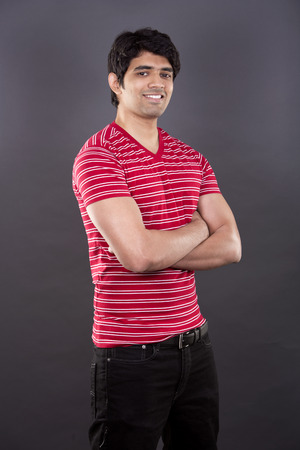 east indian: handsome east indian man wearing red shirt on light grey background