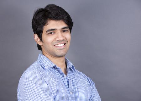 east indian: handsome east indian man wearing blue shirt on light grey background