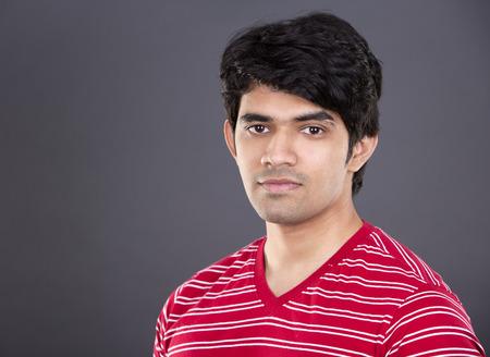 밝은 회색 배경에 빨간색 셔츠를 입고 잘 생긴 동쪽 인도 사람