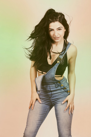 skinny woman: pretty brunette with long hair wearing jeans and leather top Stock Photo
