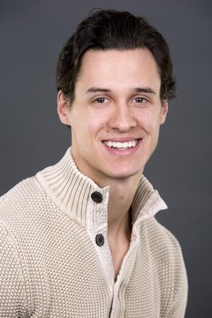 회색 배경에 베이지 색 스웨터를 쓰고 잘 생긴 백인 남자