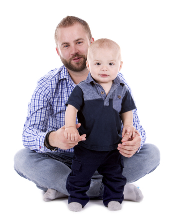 casual father and son sitting on white isolated background