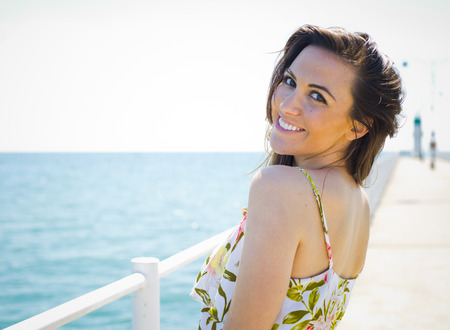 young woman smiling: young brunette wearing summer outfit on the beach