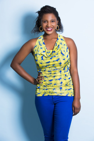 african fashion: young black woman wearing casual outfit on light blue background