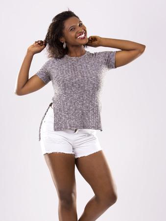 mujer bonita: mujer joven negro que llevaba traje casual en fondo gris claro