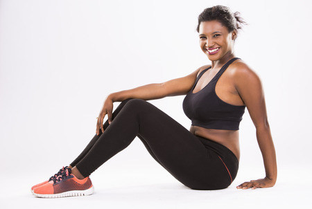 women sport: young black woman wearing fitness outfit on white isolated background