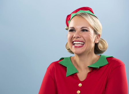 seasonal worker: blonde woman wearing elf christmas costume on blue background