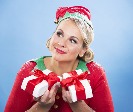 seasonal worker: blonde woman wearing elf christmas costume on white background