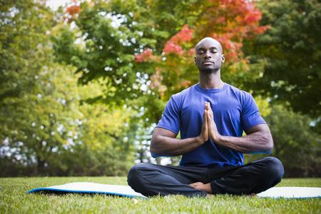 요가 운동 공원에 앉아 운동 착용 입고 젊은 흑인 남자