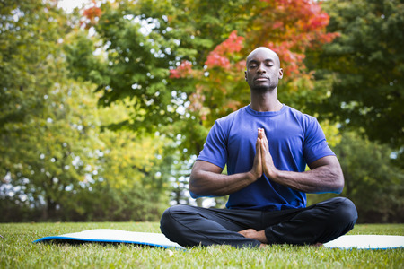 young black man wearing athletic wear sitting in the park exercising yoga Фото со стока - 64666508